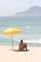 140px-Man_sitting_under_beach_umbrella.jpg