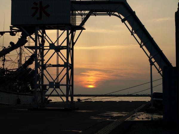 出漁間近の船に氷を~の装置?の向こうに夕陽が~~