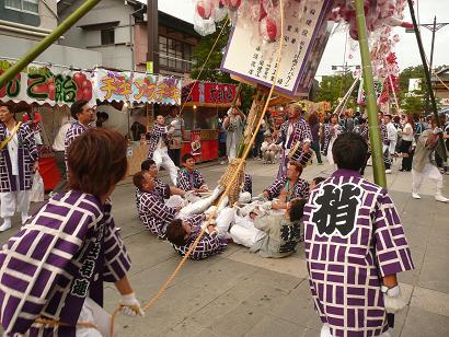 大竹の柱を必死に支える若者