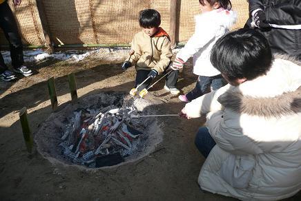 小屋で餅を焼く子供達